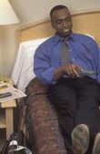Empresario mirando televisión en habitación — Foto de Stock