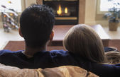 Couple Snuggles By Fireplace — Stock Photo