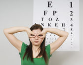 Woman Standing In Front Of Eye Chart — Stock Photo