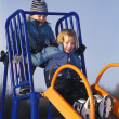 Stockfoto: Children ride on slide