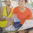 Two Girl Friends Looking At A Map In Front Of A Tent — Stock Photo