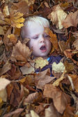 A little boy lies in leaf pile — Stock Photo