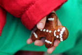A boy holds a Gingerbread cookie man in his hand — Stock Photo