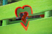 Red Heart on green fence — Stock fotografie