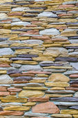 Layers of colorful stones wall as texture in vertical view — Stock Photo