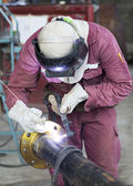 Craftman in a safety suit is welding a metal pipe — Stock Photo
