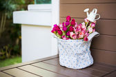 Roses with a small watering pot in fabric vase — Stock Photo