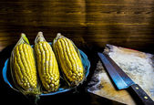 Still Life image of corncob and a knife on wooden chopping board — Stock Photo