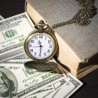 Still life image of pocket watch on bills and old book — Stock Photo #41103521