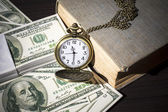 Still life image of pocket watch on bills and old book — Stock Photo