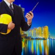 Construction engineer with a yellow helmet transmits by radio — Stock Photo