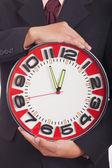 Uomo che tiene un grande orologio rosso — Foto Stock
