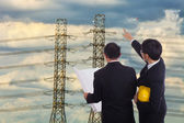 Two engineers on the background of high-voltage wires — Stock Photo