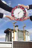 Two engineers hold large red clock — Stock Photo