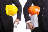 Construction engineers with helmets and documents — Stock Photo
