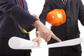 Construction engineer with helmets considering a draft — Stock Photo