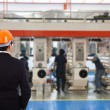 Engineer in a helmet stands on the background of the production — Stock Photo