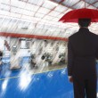 Businessman with an umbrella standing against the background of production — Stockfoto