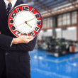 Businessman with a big red clock on the background of the plant — Stockfoto