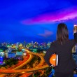 Engineer woman shows an index finger in the direction of the city at night — Stock Photo