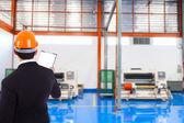 Бизнесмен с шлем стоит внутри завода — Стоковое фото
