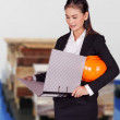 Female engineer holding an orange hard hat and a folder with documents — Stock Photo #33722601