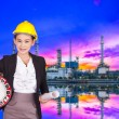 Engineer woman in yellow helmet holding a large clock and the project plan on a background of an Oil refinery — Stock Photo