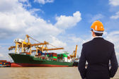 Businessman in a red helmet looks at port — Stock Photo