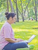 Women working on her notebook in the garden — Foto de Stock