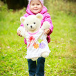 Little girl in the forest with bear — Stock Photo