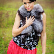 Beautiful girl in a red skirt and a fur vest in the forest — Stock Photo