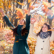 Girls playing with leaves in the autumn park — Stock Photo #34003193