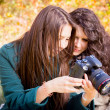 Girls looking photographs on the camera in the autumn park — Stock Photo