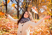Girl playing with leaves in the autumn park — Stock Photo