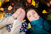 Girls lying on the grass in the autumn park — Foto Stock