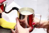 Weiblich kochende milch für cappuccino — Stockfoto