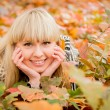Young woman in leaves — Stock Photo