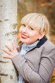 Pretty blonde hugging tree — Stock Photo