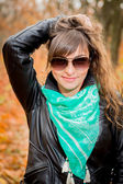 Smiling girl wearing scarf and sunglasses — Stock Photo