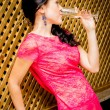 Girl in pink dress drinking champagne — Stock Photo