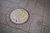 Round steel sewer manhole — Stock Photo