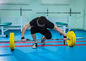 Sportsman pushing barbell — Stock Photo