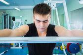 Sportsman pushing barbell — Stock Photo