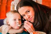 Moeder haar zoon voeden met een lepel — Stockfoto