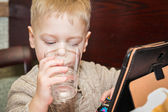Boy drinking water with tablet computer — Stock Photo