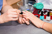 Beautician applying blue nail varnish to the fingernails of a client — Stock Photo
