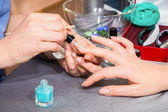 Beautician applying blue nail varnish to the fingernails of a client — ストック写真