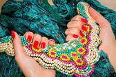 Kvinnliga händer med rött manikyr håller färgglada halsband — Stockfoto