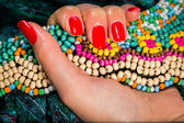 Female hand with red manicure holding colorful necklace — Stock Photo
