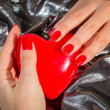 Hand with red manicure holding red heart — Stock Photo